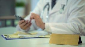 Παθολόγος στον ομοιόμορφο texting ασθενή στο smartphone, κενή πινακίδα στον πίνακα φιλμ μικρού μήκους