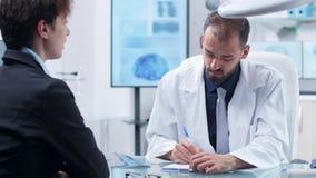 Παθολόγος στο σύγχρονο κέντρο γραφείων ή ερευνητικοου που παίρνει τις σημειώσεις από μια νέα γυναίκα φιλμ μικρού μήκους