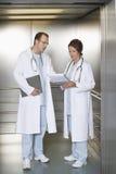 Παθολόγοι που συζητούν το διάγραμμα στον ανελκυστήρα νοσοκομείων Στοκ φωτογραφία με δικαίωμα ελεύθερης χρήσης