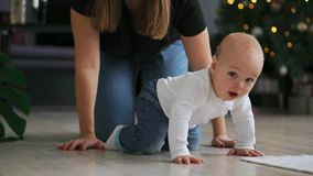 Παιδάκι με το παιχνίδι στο στόμα που σέρνεται στον καναπέ Κλείστε επάνω του γυμνού μωρού στις πάνες που περπατά στο κρεβάτι με το φιλμ μικρού μήκους