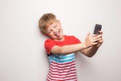 Παιδάκι που παίρνει ένα selfie με το τηλέφωνο κυττάρων που απομονώνεται στο άσπρο υπόβαθρο Πορτρέτο στούντιο στοκ εικόνες