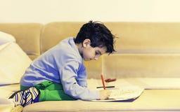 Παιδί αγοριών λίγος χρωματισμός ζωγραφικής μικρών παιδιών και σχεδιασμός με τα κραγιόνια καθμένος στον καναπέ ή το κρεβάτι στο σπ στοκ φωτογραφίες με δικαίωμα ελεύθερης χρήσης
