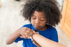Παιδί αφροαμερικάνων που ελέγχει το χρόνο στο ψηφιακό wristwatch Στοκ Φωτογραφίες