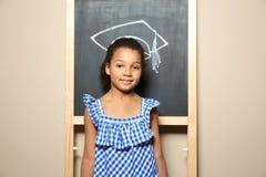 Παιδί αφροαμερικάνων που στέκεται στον πίνακα με συρμένη την κιμωλία ακαδημαϊκή ΚΑΠ Εκπαίδευση στοκ φωτογραφία