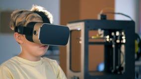 Παιδί δημοτικού σχολείου που κάνει την τρισδιάστατη τυπωμένη συσκευή που χρησιμοποιεί τα γυαλιά εικονικής πραγματικότητας απόθεμα βίντεο