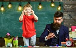Παιδί εύθυμο και ζωγραφική δασκάλων, σχεδιασμός Ο ταλαντούχος καλλιτέχνης ξοδεύει το χρόνο με το γιο Ο δάσκαλος με τη γενειάδα, π στοκ φωτογραφίες με δικαίωμα ελεύθερης χρήσης