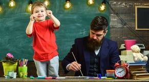 Παιδί εύθυμο και ζωγραφική δασκάλων, σχεδιασμός Ο ταλαντούχος καλλιτέχνης ξοδεύει το χρόνο με το γιο Έννοια μαθήματος τέχνης Δάσκ στοκ φωτογραφίες