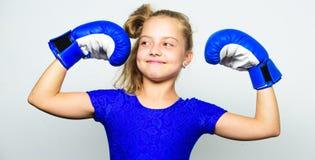 Παιδί ισχυρό και υγιές Παιδί κοριτσιών ισχυρό με τα εγκιβωτίζοντας γάντια που θέτουν στο γκρίζο υπόβαθρο Αισθάνεται ισχυρή και αν στοκ εικόνα