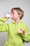 παιδί κέικ αγοριών που πίνει τρώγοντας το γάλα στοκ εικόνες