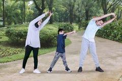 Παιδί και γονείς που κάνουν το τέντωμα χεριών στο πάρκο στοκ εικόνες με δικαίωμα ελεύθερης χρήσης