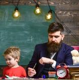 Παιδί και δάσκαλος στα πολυάσχολα πρόσωπα που χρωματίζουν, σχεδιασμός Δάσκαλος με τη γενειάδα, πατέρας και λίγος γιος στην τάξη σ στοκ εικόνα με δικαίωμα ελεύθερης χρήσης