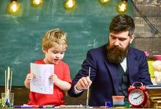 Παιδί και δάσκαλος στα πολυάσχολα πρόσωπα που χρωματίζουν, σχεδιασμός Έννοια μαθήματος σχεδίων Δάσκαλος με τη γενειάδα, πατέρας κ στοκ φωτογραφία