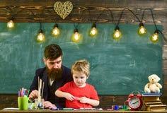 Παιδί και δάσκαλος στα πολυάσχολα πρόσωπα που χρωματίζουν, σχεδιασμός Δάσκαλος με τη γενειάδα, πατέρας και λίγος γιος στην τάξη σ στοκ φωτογραφίες