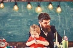 Παιδί και δάσκαλος στα πολυάσχολα πρόσωπα που χρωματίζουν, σχεδιασμός Δάσκαλος με τη γενειάδα, πατέρας και λίγος γιος στην τάξη σ στοκ εικόνες