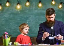 Παιδί και δάσκαλος στην πολυάσχολη ζωγραφική προσώπου, σχεδιασμός Δάσκαλος με τη γενειάδα, σχέδιο πατέρων ενώ λίγος γιος κρεμά έξ στοκ φωτογραφία