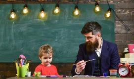 Παιδί και δάσκαλος στην πολυάσχολη ζωγραφική προσώπου, σχεδιασμός Ο δάσκαλος με τη γενειάδα, πατέρας διδάσκει λίγο γιο για να σύρ στοκ εικόνες