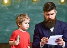 Παιδί και δάσκαλος στην πολυάσχολη ζωγραφική προσώπου, σχεδιασμός Ο δάσκαλος με τη γενειάδα, πατέρας διδάσκει λίγο γιο για να σύρ στοκ εικόνα με δικαίωμα ελεύθερης χρήσης