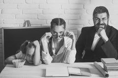 Παιδί και οι δάσκαλοί της με τα κουρασμένα, δυσνόητα και βέβαια πρόσωπα Στοκ Εικόνες