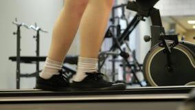Παιδί κινηματογραφήσεων σε πρώτο πλάνο μελών του σώματος ποδιών που περπατά treadmill στον αθλητισμό που εκπαιδεύει το δωμάτιο ικ απόθεμα βίντεο