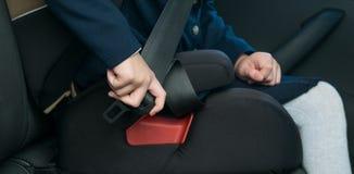 Παιδί-κορίτσι σε ένα κάθισμα παιδιών, συνδετήρες επάνω ανεξάρτητα, όντας στο αυτοκίνητο, πριν από το ταξίδι στοκ εικόνα