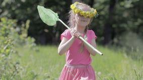 Παιδί με ένα καθαρό τρέξιμο πεταλούδων μέσω ενός δασικού ξέφωτου, στο κεφάλι ενός στεφανιού των πικραλίδων απόθεμα βίντεο