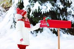 Παιδί με την επιστολή σε Santa στην ταχυδρομική θυρίδα Χριστουγέννων στο χιόνι Στοκ Εικόνα