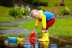 Παιδί με τη βάρκα εγγράφου στη λακκούβα Παιδιά από τη βροχή στοκ εικόνα
