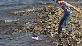 Παιδί με τη βάρκα εγγράφου στο νερό στην παραλία Το παιδί μικρών παιδιών βάζει το σκάφος εγγράφου στην επιφάνεια θάλασσας Ναυσιπλ απόθεμα βίντεο
