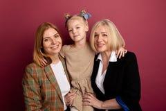 Παιδί με τη μητέρα και τη γιαγιά μαζί να χαμογελάσει και αγκάλιασμα που απομονώνονται στοκ φωτογραφία