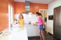 Παιδί με τις ακατέργαστες πατάτες που φαίνεται χαμογελώντας δίπλα στη μητέρα στο kitche στοκ φωτογραφίες