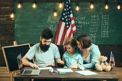 Παιδί με τους γονείς στην τάξη με την αμερικανική σημαία, πίνακας κιμωλίας στο υπόβαθρο Η αμερικανική οικογένεια κάθεται στο γραφ Στοκ Φωτογραφία