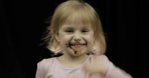 Παιδί με το βρώμικο πρόσωπο από τη λειωμένη σοκολάτα και το κτυπημένο χαμόγελο κρέμας φιλμ μικρού μήκους
