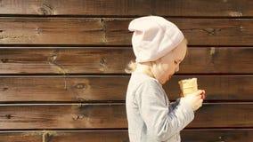 Παιδί με το παγωτό διαθέσιμο στο ξύλινο υπόβαθρο απόθεμα βίντεο