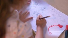 Παιδί με το mom που επισύρει την προσοχή σε χαρτί, μητέρα που βοηθά την κόρη με την εργασία, που κάθεται στον πίνακα, οικογενειακ απόθεμα βίντεο