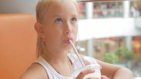 Παιδί μικρών κοριτσιών στο κακάο κοκτέιλ πόσιμου γάλακτος καφέδων με το γάλα Το παιδί πίνει ένα milkshake κάθεται σε έναν καφέ απόθεμα βίντεο