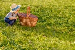 Παιδί μικρών παιδιών υπαίθρια Αγοράκι ενός έτους βρεφών που φορά το καπέλο αχύρου που κοιτάζει στο καλάθι πικ-νίκ Στοκ Εικόνες