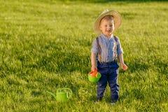 Παιδί μικρών παιδιών υπαίθρια Το αγοράκι ενός έτους βρεφών που φορά το καπέλο αχύρου που χρησιμοποιεί το πότισμα μπορεί στοκ εικόνα με δικαίωμα ελεύθερης χρήσης