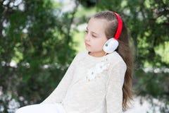Παιδί μόδας και σύγχρονη τεχνολογία Ήχος και mp3 μελωδίας Το μικρό κορίτσι ακούει μουσική στο θερινό πάρκο Το παιδί απολαμβάνει τ Στοκ εικόνες με δικαίωμα ελεύθερης χρήσης