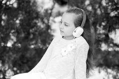Παιδί μόδας και σύγχρονη τεχνολογία Ήχος και mp3 μελωδίας Το μικρό κορίτσι ακούει μουσική στο θερινό πάρκο Το παιδί απολαμβάνει τ Στοκ Φωτογραφίες