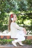Παιδί μόδας και σύγχρονη τεχνολογία Το μικρό κορίτσι ακούει μουσική στο θερινό πάρκο Το παιδί απολαμβάνει τη μουσική στα ακουστικ Στοκ Εικόνες