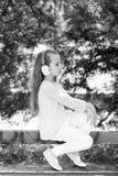 Παιδί μόδας και σύγχρονη τεχνολογία Το μικρό κορίτσι ακούει μουσική στο θερινό πάρκο Το παιδί απολαμβάνει τη μουσική στα ακουστικ Στοκ Φωτογραφίες