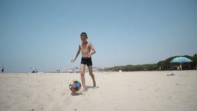 Παιδί που έχει τη διασκέδαση στην παραλία στο ηλιοβασίλεμα που κλωτσά μια σφαίρα ποδοσφαίρου Στοκ Εικόνα