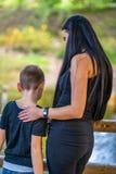 Παιδί που αγκαλιάζει το Mom του στη γέφυρα σε ένα πάρκο στοκ εικόνες