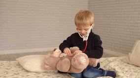 Παιδί που ακούει τον κτύπο της καρδιάς της teddy αρκούδας με το στηθοσκόπιο σε μια κρεβατοκάμαρα φιλμ μικρού μήκους