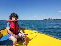 Παιδί που αλιεύει από τη μικρή λέμβο στο λιμάνι Tauranga Στοκ Εικόνα