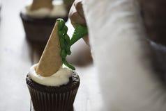 Παιδί που βάζει την πράσινη τήξη σε ένα cupcake Στοκ εικόνα με δικαίωμα ελεύθερης χρήσης