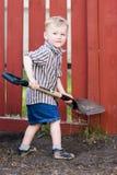 παιδί που βοηθά το φτυάρι Στοκ Φωτογραφίες