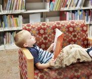 Παιδί που διαβάζει ένα βιβλίο σε έναν καναπέ στη βιβλιοθήκη στοκ φωτογραφία