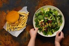 Παιδί που κάνει την επιλογή μεταξύ της υγιών σαλάτας και του γρήγορου φαγητού Στοκ εικόνα με δικαίωμα ελεύθερης χρήσης
