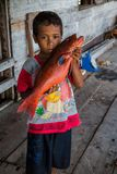 Παιδί που κρατά ένα ζωηρόχρωμο ψάρι Kerapu στοκ φωτογραφία